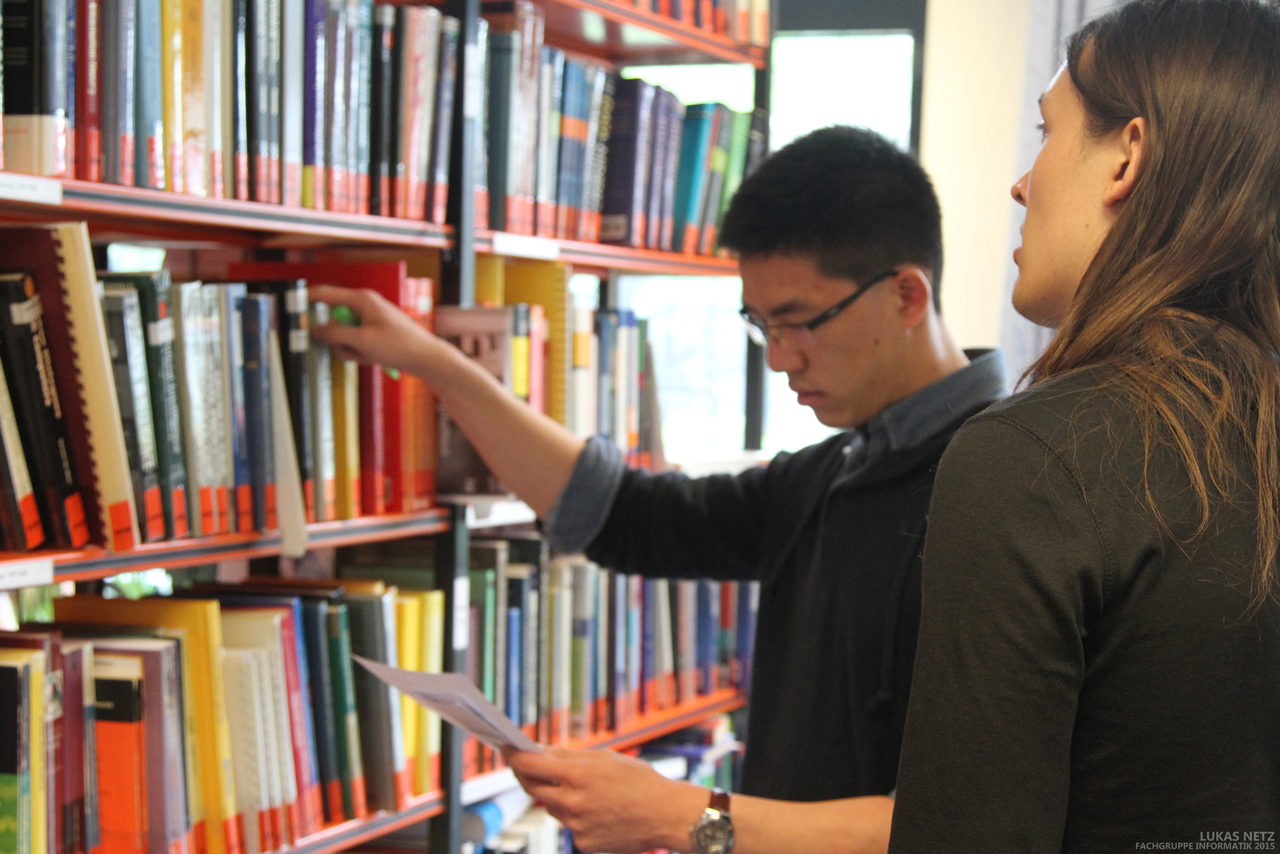 Students remove books from a bookcase
