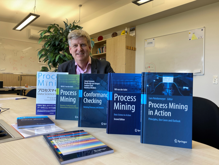 Wil van der Aalst sits in front of a desk, multiple books on Process Mining are placed in front of him